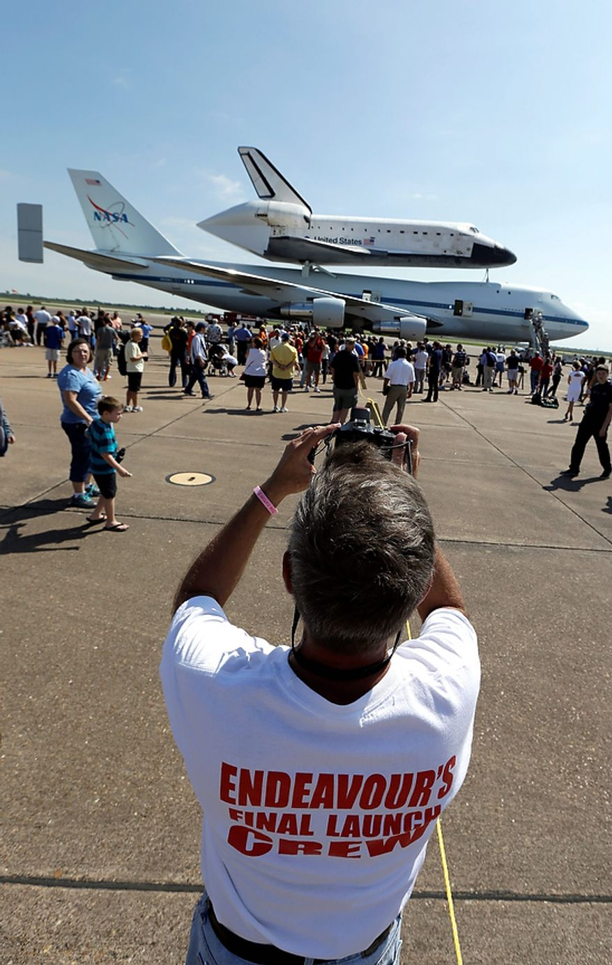 Scott Rush photographs space shuttle Endeavour as it atop the shuttle aircraft carrier after landing Wednesday, Sept. 19, 2012, at Ellington Field in Houston. Endeavour is making a final trek across the country to the California Science Center in Los Angeles, where it will be permanently displayed. (AP Photo/David J. Phillip
