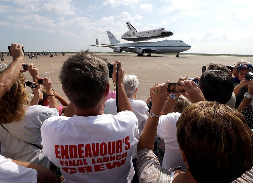 Scott Rush, left, photographs space shuttle Endeavour atop the shuttle aircraft carrier after landing Wednesday, Sept. 19, 2012, at Ellington Field in Houston. Endeavour is making a final trek across the country to the California Science Center in Los Angeles, where it will be permanently displayed. (AP Photo/David J. Phillip)