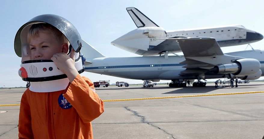 Joey Morrison adjusts his space helmet after watching the shuttle aircraft carrier with space shuttle Endeavour atop, land Wednesday, Sept. 19, 2012, at Ellington Field in Houston. Endeavour is making a final trek across the country to the California Science Center in Los Angeles, where it will be permanently displayed. (AP Photo/David J. Phillip