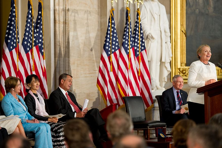 Chairperson and General Secretary of the National League for Democracy Aung San Suu Kyi of Myanmar, also known as Burma, second from left, sits between House Democratic Leader Nancy Pelosi (D-Calif.), left, and Speaker of the House John Boehner (R-Ohio), right, as  Secretary of State Hillary Rodham Clinton, right, speaks during a ceremony to award Suu Kyi the Congressional Gold Medal  in the Capitol rotunda, Washington, D.C., Wednesday, September 19, 2012. (Andrew Harnik/The Washington Times)