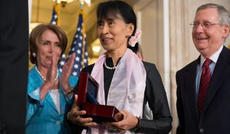 Myanmar opposition leader Aung San Suu Kyi (center) is awarded the Congressional Gold Medal in the Rotunda of the U.S. Capitol in Washington on Sept. 19, 2012, as House Democratic Leader Nancy Pelosi, California Democrat, and Senate Republican Leader Mitch McConnell, Kentucky Republican, look on. (Andrew Harnik/The Washington Times)