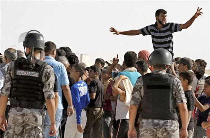 Syrian refugees chant slogans to protest against the visit of Lakhdar Brahimi, the U.N.-Arab League envoy to Syria, not pictured, to the Zaatari Refugees Camp in Jordan for Syrians who fled the civil war in their country in Mafraq, Jordan, Tuesday, Sept. 18, 2012. (AP Photo/Raad Adayleh)