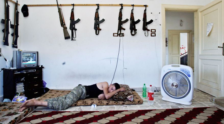 A Syrian rebel sleeps last month after fighting government forces in Aleppo. A 60-member coalition called Friends of the Syrian People, recognizing that sanctions alone will not bring down the Assad regime, is collaborating on financial strategies. (Associated Press)