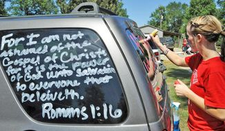 Kountze High School cheerleader Brooke Coates writes Scripture verses on a vehicle. The southeast Texas community is backing cheerleaders after they were told not to use Scripture verses on their banners at football games. The court has intervened in the issue of religion in public schools. (Associated Press)
