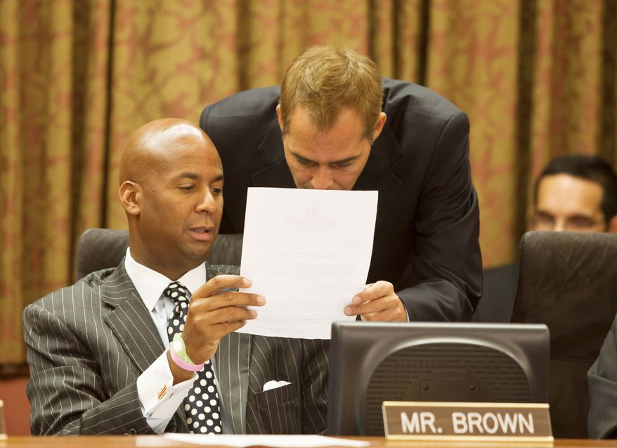 D.C. Council member Michael A. Brown confers with a staffer Wednesday during a council meeting. Mr. Brown has introduced a bill that calls for exploring public financing of political campaigns in the city. (Craig Bisacre/The Washington Times)