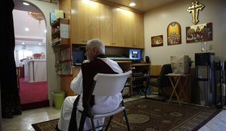 Archy Jacob sits in a sound room during a Mass at St. Mary and St. Verena Orthodox Coptic Church in Anaheim, Calif., Wednesday, Sept. 19, 2012. (AP Photo/Jae C. Hong)