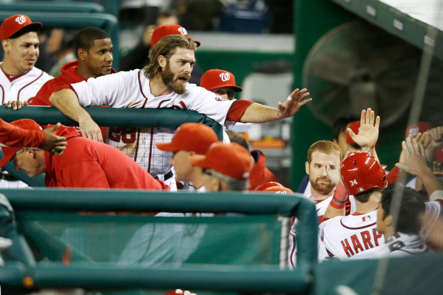 Washington Nationals Bryce Harper, right, is high fived by teammates after scoring on a double from Ryan Zimmerman, against the Los Angeles Dodgers during the third inning. (AP Photo/Jacquelyn Martin)