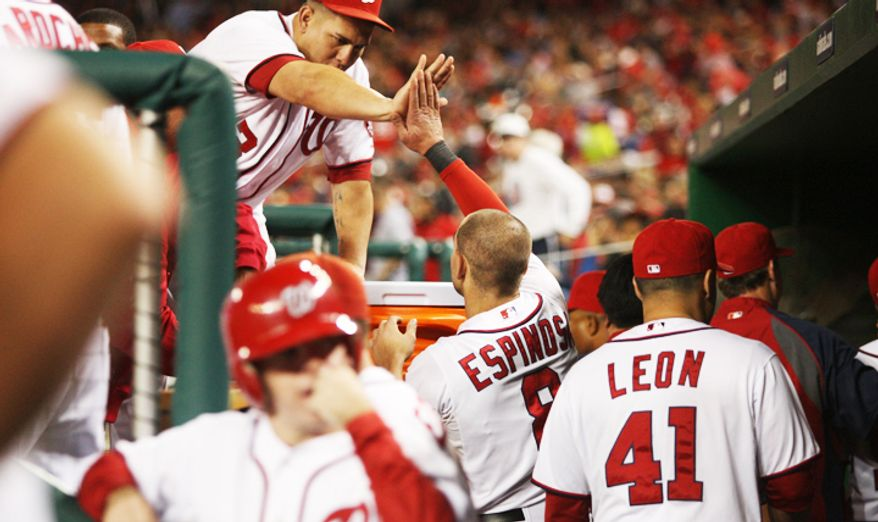 Washington Nationals second baseman Danny Espinosa (8) celebrates in the dugout after scoring on a sacrifice fly out by catcher Kurt Suzuki (24) in the fourth inning. (Craig Bisacre/The Washington Times)
