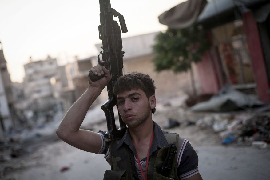 A Free Syrian Army fighter stands at the front line in the Amariya district in Aleppo, Syria, on Wednesday, Sept. 19, 2012. (AP Photo/Manu Brabo)