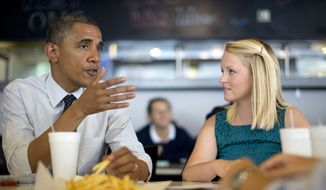 President Obama talks with Emily Young, first-time voter and student at University of Miami, on Sept. 20, 2012, at OMG Burger in Miami. (Associated Press)