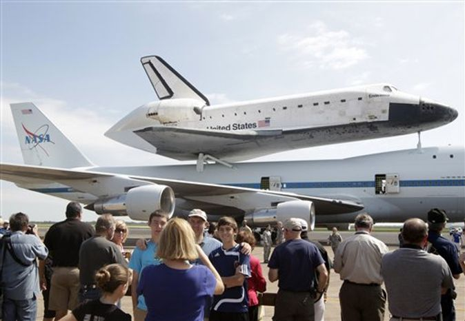 A large crowd takes photographs of the Space Shuttle Endeavour sitting atop NASA's 747 Shuttle Carrier Aircraft at Ellington Field in Houston on Wednesday, Sept. 19, 2012. Endeavour will spend the night in Houston before continuing its journey from the Kennedy Space Center in Florida to the California Science Center in Los Angeles where it will be on permanent display. (AP Photo/The Galveston County Daily News, Kevin M. Cox)