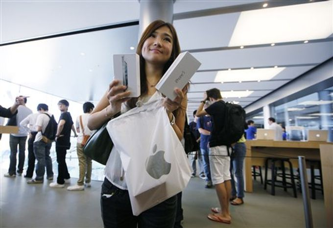 A customer shows her new iPhone 5 at the Apple store in Hong Kong on Sept. 21, 2012. Apple's Asian fans jammed the tech juggernaut's shops in Australia, Hong Kong, Japan and Singapore to pick up the latest version of its iPhone. (Associated Press)