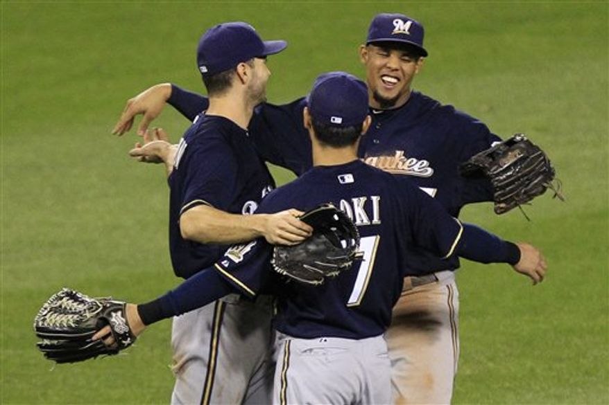 Milwaukee Brewers left fielder Ryan Braun, left, Milwaukee Brewers center fielder Carlos Gomez, right, and Milwaukee Brewers right fielder Norichika Aoki (7) celebrate after a 9-7 win over the Pittsburgh Pirates in a baseball game in Pittsburgh, Thursday, Sept. 20, 2012. (AP Photo/Gene J. Puskar)