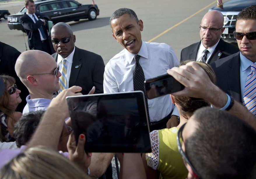 President Obama greets people Sept. 20, 2012, on the tarmac as he arrives on Air Force One at Tampa International Airport in Tampa. (Associated Press)