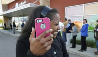 Western Michigan University student Alenna Brown ,19, leaves with her new iPhone 5 in Kalamazoo, Mich. on Friday, Sept. 21, 2012. (AP Photo/The Kalamazoo Gazette, Mark Bugnaski)