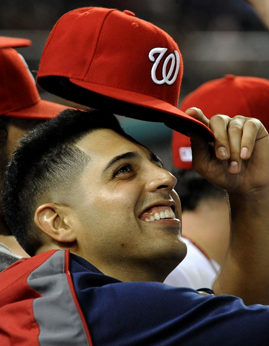 Washington Nationals' starting pitcher Gio Gonzalez relaxes in the dugout after pitching seven innings of shutout baseball against the Chicago Cubs during their baseball game at Nationals Park, Wednesday, Sept. 5, 2012, in Washington. Gonzalez won his eighteenth game of the season. (AP Photo/Richard Lipski)