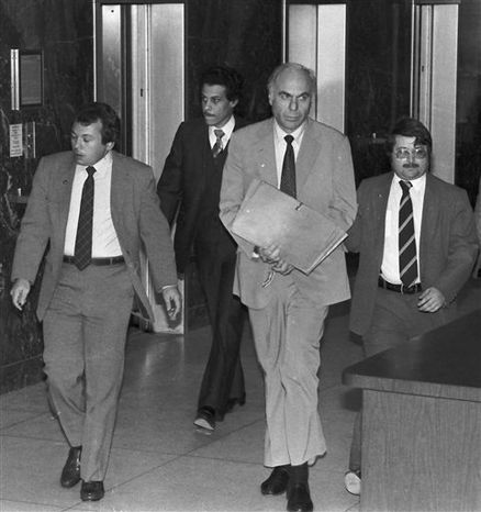 ** FILE ** In this Jan. 22, 1983, file photo, ex-CIA agent Edwin Wilson, center, leaves federal court after a day of jury selection accompanied by U.S. Marshals in Houston. Wilson, who was branded a traitor and convicted of shipping arms to Libya but whose conviction was later overturned after he served 22 years in prison, died on Sept. 10, 2012. He was 84. (AP Photo/File)