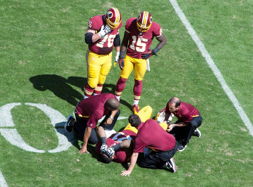 Washington Redskins tackle Trent Williams is tended to after suffering a right knee injury during the first quarter. Williams played sparingly after that in the 38-31 loss to Cincinnati. (Craig Bisacre/The Washington Times)