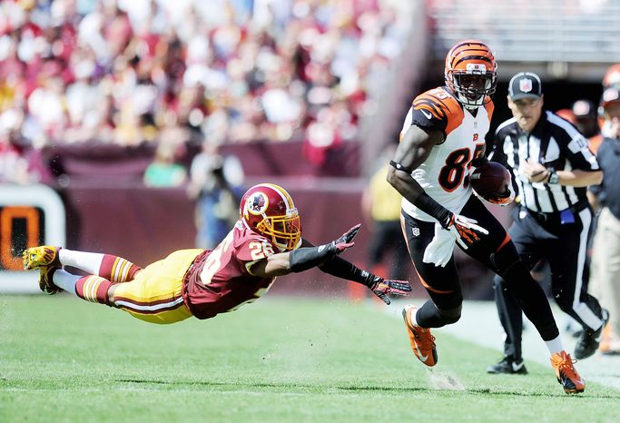 Redskins cornerback Josh Wilson comes up empty in his attempt to bring down Bengals receiver Armon Binns. Regularly let down by the secondary, Washington has allowed more than 30 points in each of its three games to kick off this season. (Preston Keres/Special to The Washington Times)
