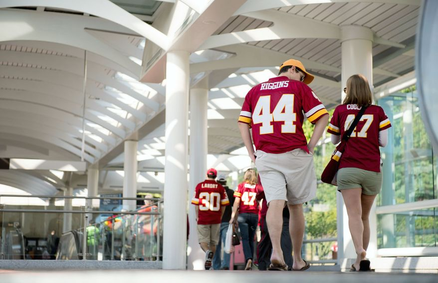 Fans walk to the Redskins game from the Morgan Boulevard Metro Station on Sunday. Taking Metro is an option for fans getting to and leaving the game, but they still face a walk. (Andrew Harnik/The Washington Times)