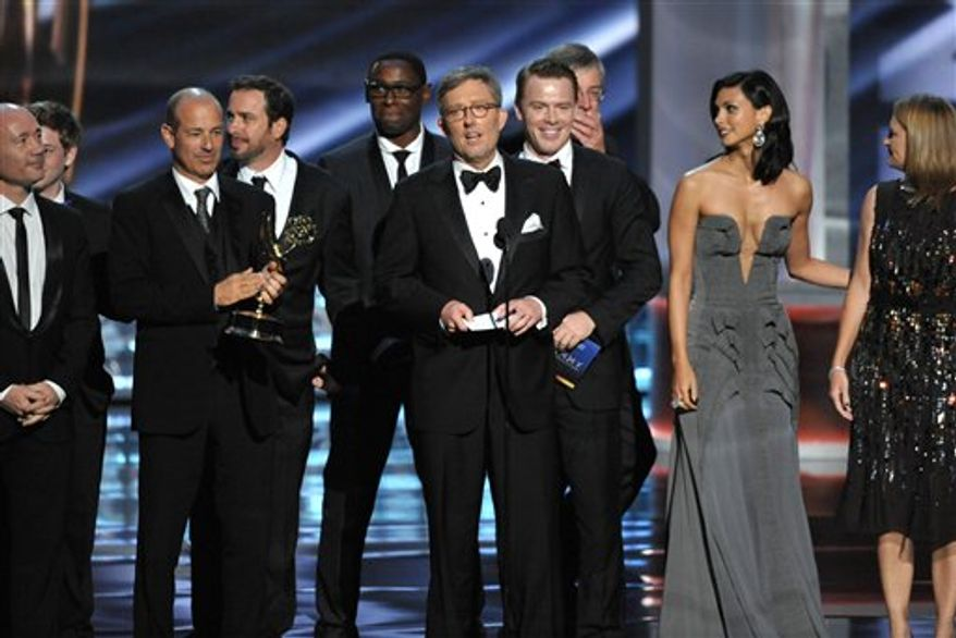 """Alex Gansa (center) and the cast and crew of """"Homeland"""" accept the award for outstanding drama series at the 64th Primetime Emmy Awards at the Nokia Theatre on Sunday, Sept. 23, 2012, in Los Angeles. (John Shearer/Invision/AP)"""