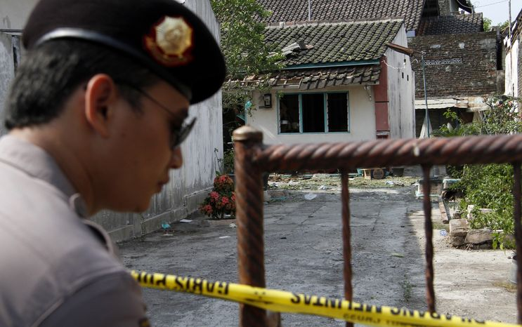 An Indonesian police officer stands guard outside the house of a suspected militant after a police raid in Solo, Indonesia, on Saturday, Sept. 22, 2012. An elite Indonesian anti-terror squad has arrested 10 Islamic militants and seized a dozen homemade bombs from a group suspected of planning suicide attacks against security forces and the government, police said Sunday. (AP Photo/A.K. Hendratmo)