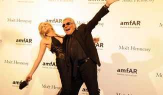 Actress Sharon Stone (left) and Italian fashion designer Roberto Cavalli pose at the amfAR Foundation for AIDS Research charity event, part of the Fashion Week in Milan, on Saturday, Sept. 22, 2012. (AP Photo/Giuseppe Aresu)