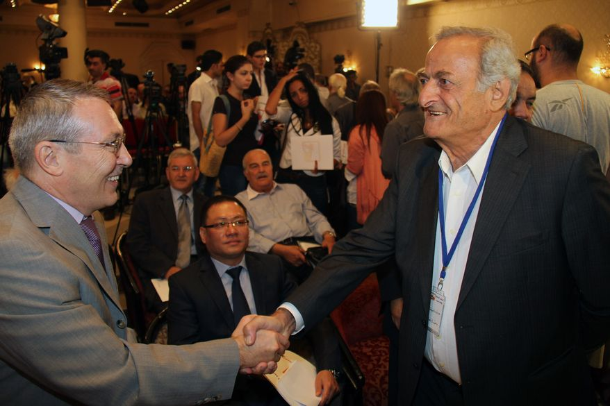 Azmat Allah Kolmahmedov (left), the Russian ambassador to Syria, greets Aref Dalila, a Syrian opposition figure, at the opening session of a conference of some 16 opposition parties headed by the National Coordination Body for Democratic Change in Syria in Damascus, Syria, on Sept. 23, 2012. (AP Photo/Bassem Tellawi)