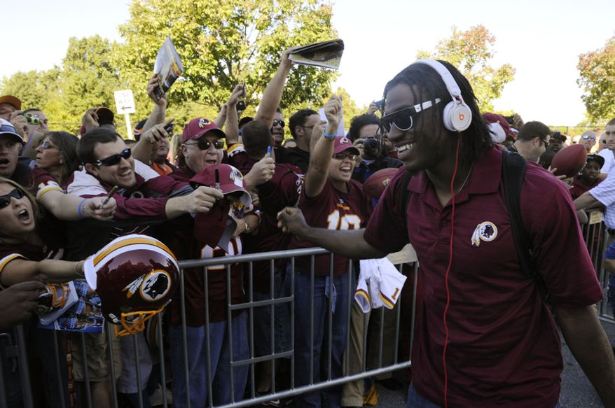 Washington Redskins quarterback Robert Griffin III signs autographs for the fans as he arrives to FedEx Field, Landover, Md., Sep. 23, 2012. (Preston Keres/Special to The Washington Times)