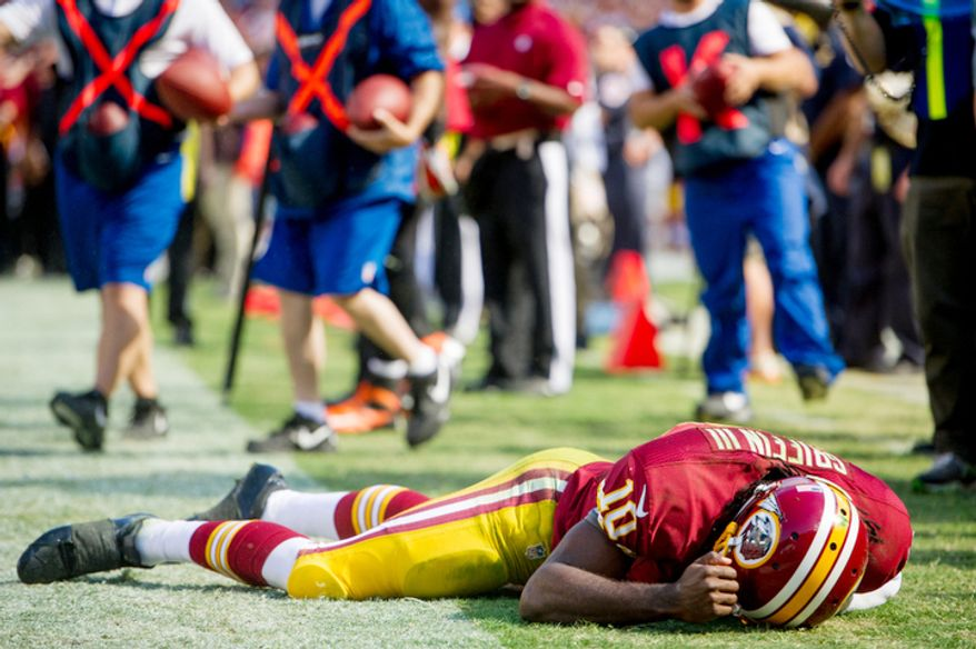 Washington Redskins quarterback Robert Griffin III (10) collapses and is slow to get up after unsuccessfully diving for the end zone in the second quarter as the Washington Redskins play the Cincinnati Bengals on their home opener at FedEx Field, Landover, Md., Sunday, September 23, 2012. (Andrew Harnik/The Washington Times)