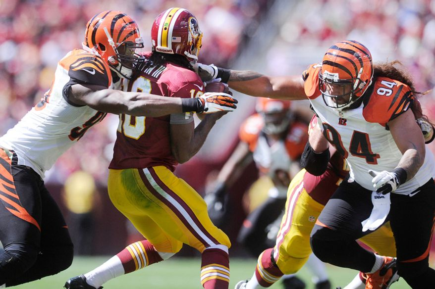 Cincinnati Bengals defensive end Michael Johnson (L) sacks Washington Redskins quarterback Robert Griffin III (10) with the help of Cincinnati Bengals defensive tackle Domata Peko (94) during first quarter action. (Preston Keres/Special to The Washington Times)