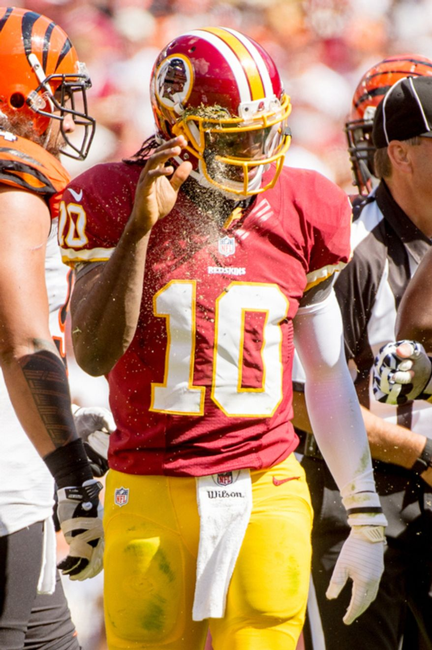 Washington Redskins quarterback Robert Griffin III (10) wipes dirt and grass from his helmet after being sacked in the second quarter. (Andrew Harnik/The Washington Times)