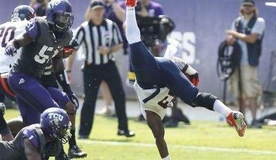 Virginia running back Perry Jones (33) is upended by TCU safety Chris Hackett (1) as linebacker Kenny Cain (51) looks on during the first half on an NCAA college football game Saturday, Sept. 22, 2012, in Fort Worth, Texas. (AP Photo/LM Otero)