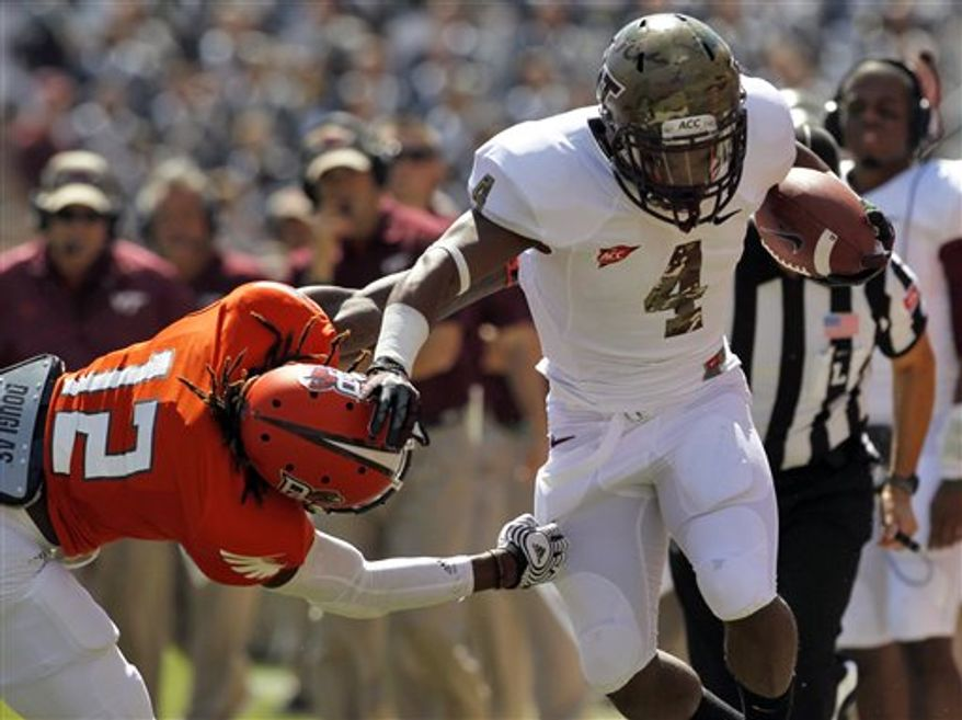 Bowling Green's DeVon McKoy (12) tries to pull down Virginia Tech's J.C. Coleman during an NCAA college football game on Saturday, Sept. 22, 2012, at Lane Stadium in Blacksburg, Va. Virginia Tech won 37-0. (AP Photo/The Roanoke Times, Rebecca Barnett)