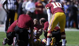 Washington Redskins tackle Trent Williams (71) sits injured on the field as quarterback Robert Griffin III (10) looks on at FedEx Field, Landover, Md., Sep. 23, 2012. (Preston Keres/Special to The Washington Times)