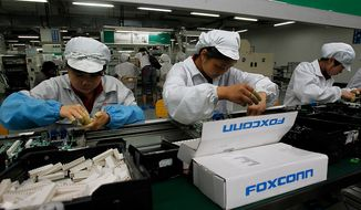 ** FILE ** Employees work on the production line at the Foxconn complex in the southern Chinese city of Shenzhen in May 2010. (AP Photo/Kin Cheung)