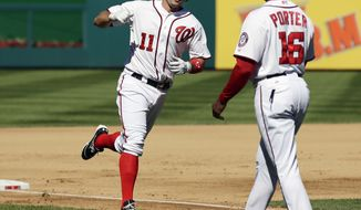 Washington Nationals' Ryan Zimmerman, left, celebrates with third base coach Bo Porter during his three run homer during the fourth inning of a baseball game against the Milwaukee Brewers at Nationals Park, Monday, Sept. 24, 2012, in Washington. The Nationals won 12-2. (AP Photo/Alex Brandon)