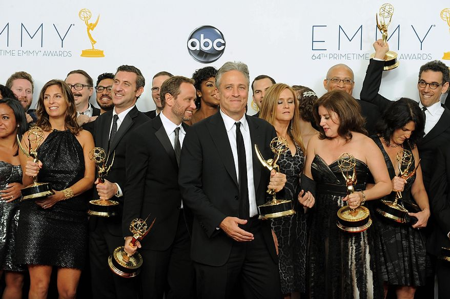 """Jon Stewart, winner Outstanding Varety Series for """"The Daily Show With Jon Stewart"""", center, poses backstage with his staff at the 64th Primetime Emmy Awards at the Nokia Theatre on Sunday, Sept. 23, 2012, in Los Angeles. (Photo by Jordan Strauss/Invision/AP)"""