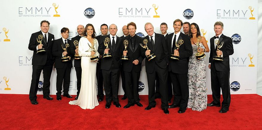 """Producer Jerry Bruckheimer, center, winner of the Emmy for Outstanding Reality-Competition Program for """"The Amazing Race,"""" poses with members of the show's crew backstage at the 64th Primetime Emmy Awards at the Nokia Theatre on Sunday, Sept. 23, 2012, in Los Angeles. (Photo by Jordan Strauss/Invision/AP)"""