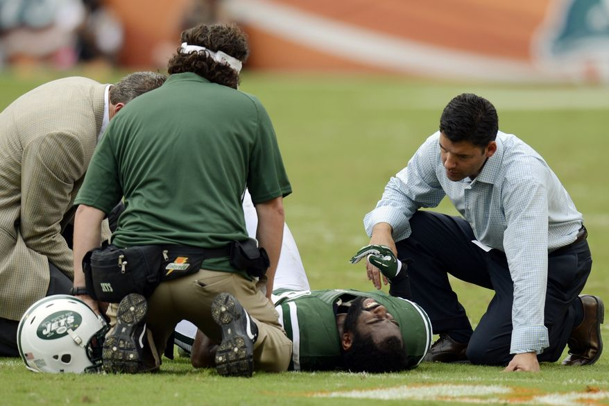 New York Jets trainers attend to cornerback Darrelle Revis (24) during the second half of an NFL football game against the Miami Dolphins, Sunday, Sept. 23, 2012, in Miami. (AP Photo/Rhona Wise)