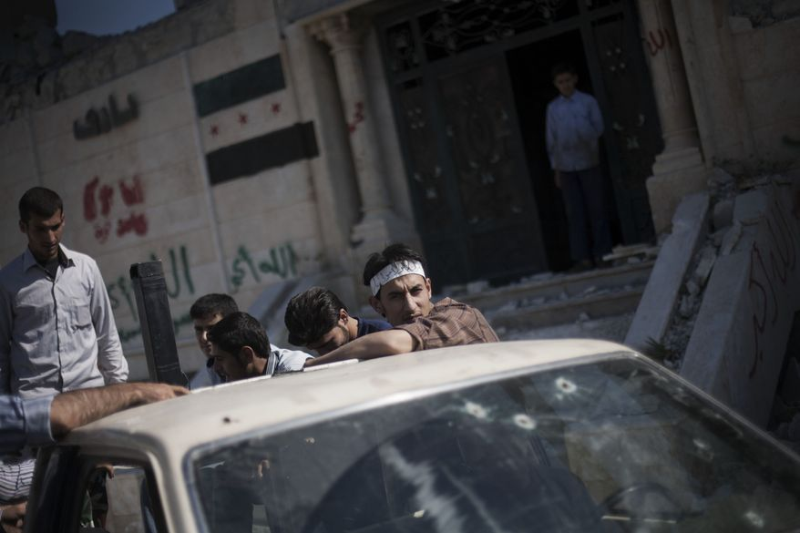 Free Syrian Army fighters are seen in a truck outside their headquarters in Aleppo, Syria, on Sunday, Sept. 23, 2012. (AP Photo/Manu Brabo)