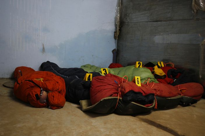 Bodies of climbers killed in an avalanche at Mount Manaslu lie covered with numbers at the Tribhuvan University Teaching hospital in Katmandu, Nepal, on Sept. 24, 2012. The avalanche killed at least nine mountaineers and injured others. (Associated Press)