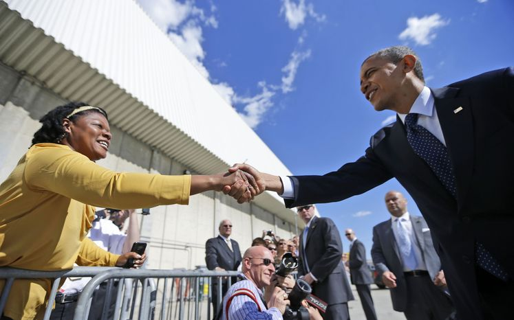 President Obama reaches over to greet a supporters on the tarmac Sept. 24, 2012, upon his arrival on Air Force One at JFK airport in New York. (Associated Press)
