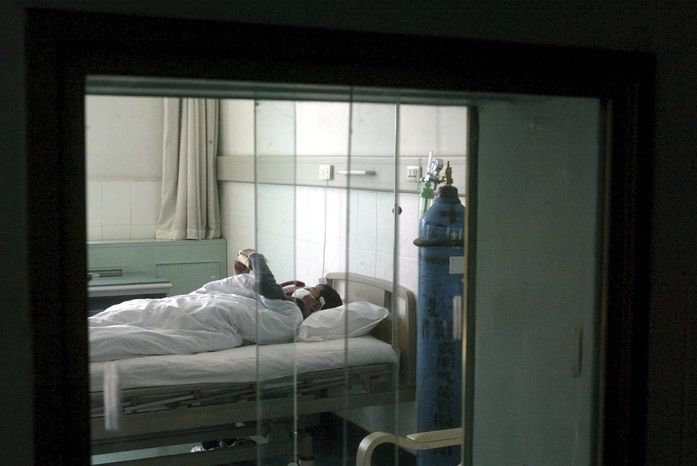 **FILE** A SARS patient receives treatment behind double-layer glass windows and strict quarantine measures at the Beijing Ditan Hospital in Beijing on April 13, 2003. (Associated Press)