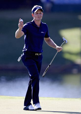 Luke Donald, of England, acknowledges the applause from the crowd after sinking his putt on the 17th hole during the final round of the Tour Championship golf tournament Sunday, Sept. 23, 2012, in Atlanta. (AP Photo/David Goldman)