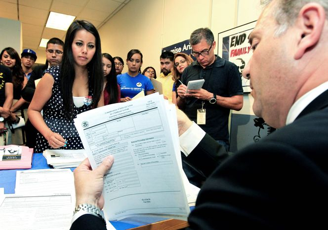 Young immigrants, including Gaby Perez (above), hand over paperwork to get guidance from immigration attorney Jose Penalosa in Phoenix. Charlene Gomez (below) conducts an orientation seminar for illegal immigrants at the Coalition for Humane Immigrant Rights in Los Angeles to determine whether they qualify for temporary work permits. (Associated Press)