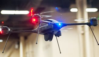 **FILE** In this Sept. 25, 2012, file photo, Lockheed Martin shows off its remote-controlled miniature drone at the Association for Unmanned Vehicle Systems International conference in Las Vegas. (Martin S. Fuentes/Special to The Washington Times)
