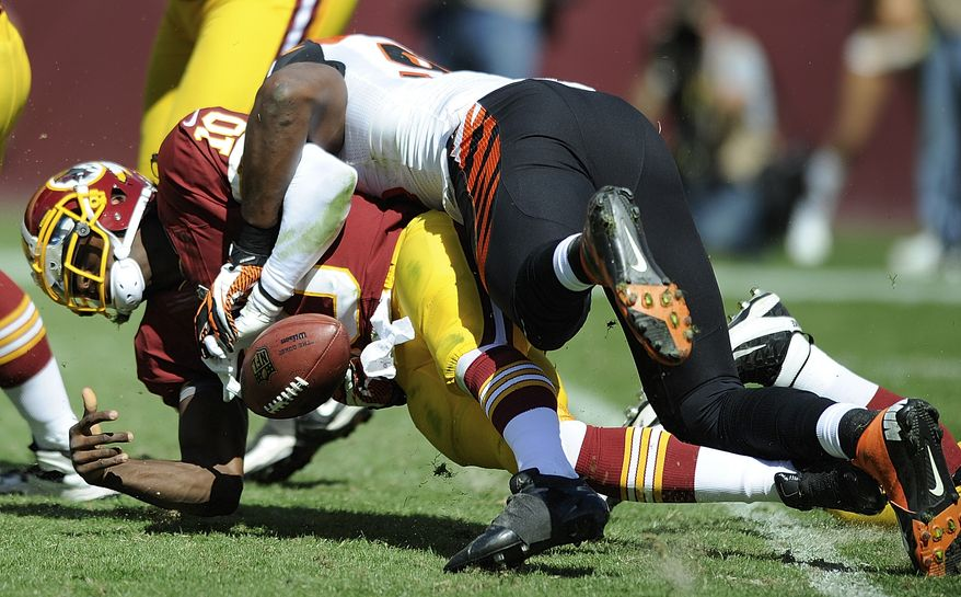 Washington Redskins quarterback Robert Griffin III is sacked by Cincinnati Bengals defensive end Michael Johnson during the first half of an NFL football game in Landover, Md., Sunday, Sept. 23, 2012. (AP Photo/Nick Wass)