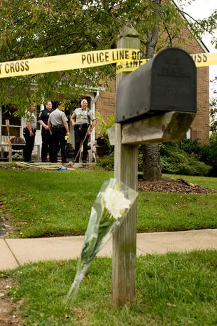 Flowers are left leaning up against a mailbox after Fairfax police officers investigate the death of four family members discovered around noon after individuals had failed to show up to work, Herndon, Va., Tuesday, September 25, 2012. (Andrew Harnik/The Washington Times)