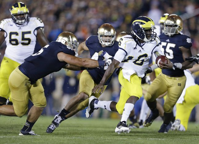 Michigan's Denard Robinson runs out of the tackle of Notre Dame's Manti Te'o (5) during the first half of an NCAA college football game Saturday, Sept. 22, 2012, in South Bend, Ind. (AP Photo/Darron Cummings)